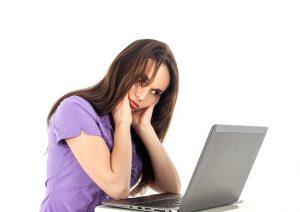 Zmartwiona kobieta przed komputerem