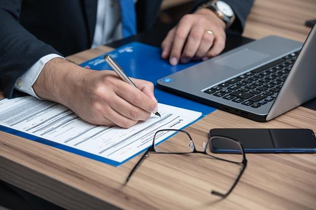 Mężczyzna podpisujący dokument